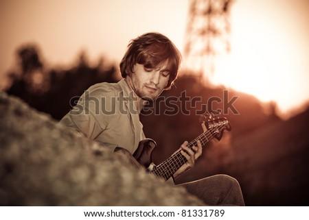 young man play guitar at sunset - stock photo