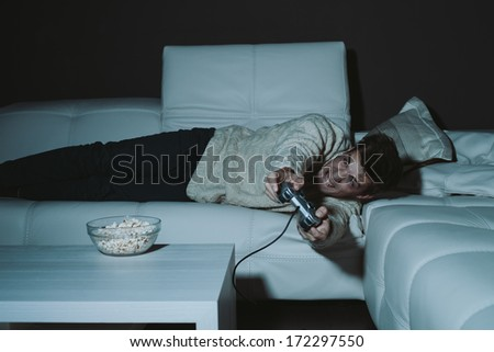 Young man playing a game at home  - stock photo