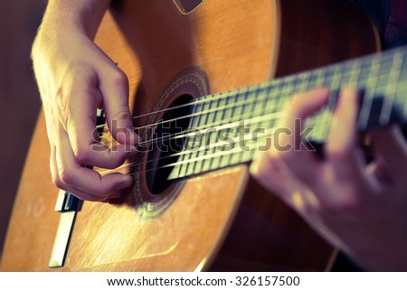 Young man playing acoustic guitar during a concert. - Vintage colours.