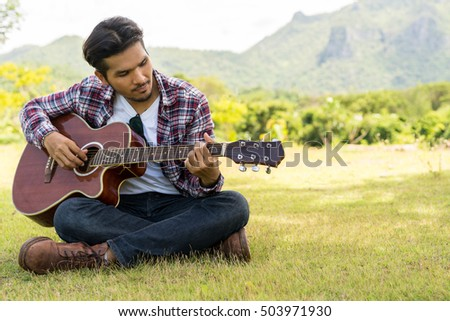 Young man playing acoustic guitar folk song, sitting on green grass. Nature background.