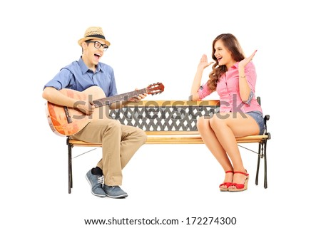 Young man playing acoustic guitar to his excited girlfriend seated on bench isolated on white background - stock photo