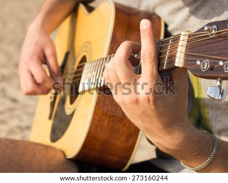 young man playing an acoustic guitar on the beach - stock photo