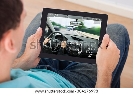 Young Man Playing Car Racing Game On Digital Tablet At Home - stock photo