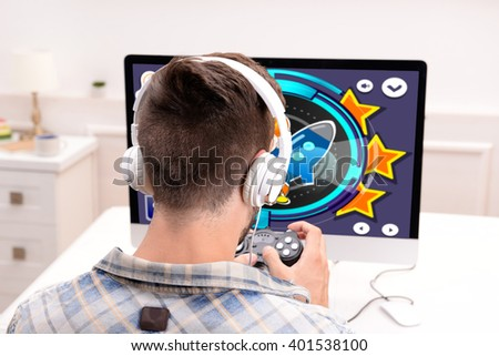 Young man playing computer games at home - stock photo