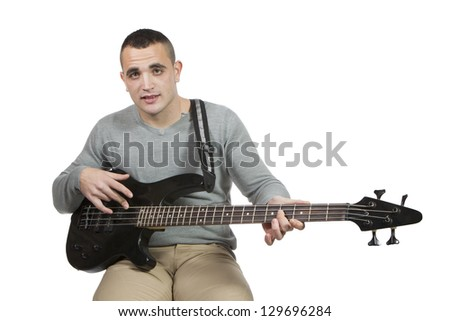 Young man playing electric bass on white background