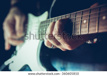 Young man playing electric guitar. Music, instrument education, entertainment, rock star, music concert   and learning concept - stock photo