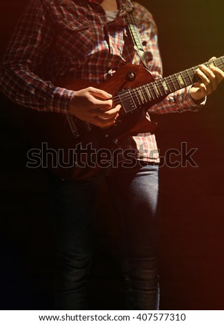 Young man playing electric guitar on dark lighted background