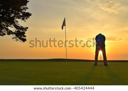 Young man playing golf at sunset - stock photo