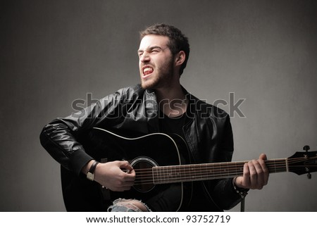 Young man playing guitar and singing