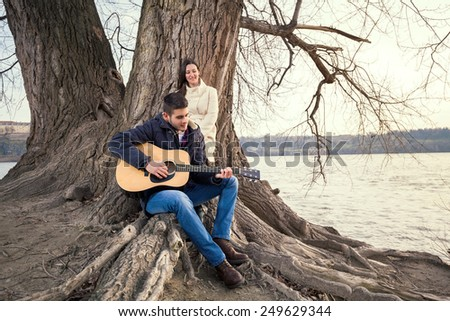 Young man playing guitar and singing to his girlfriend while sitting on the tree - stock photo