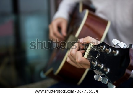 Young man playing guitar. Close up. Focus on the left hand. With shallow depth of field. - stock photo