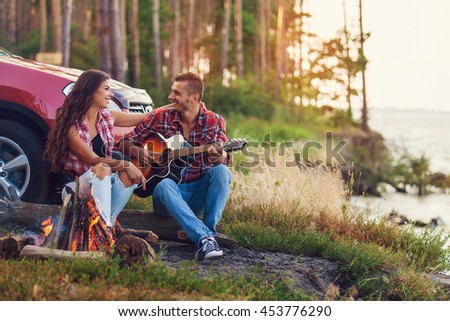 young man playing guitar for his girlfriend on a road trip - stock photo