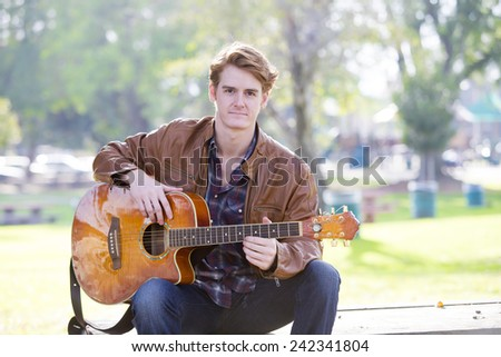 young man playing guitar in a park - stock photo