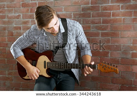Young man playing guitar on brick wall background