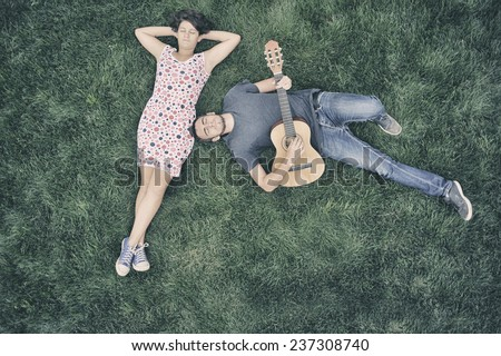 Young man playing guitar to his girlfriend in nature - dating couple - stock photo