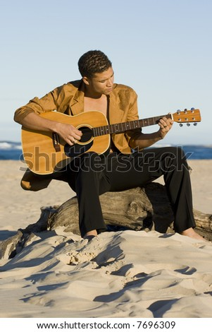 Young man playing his guitar on the beach - stock photo