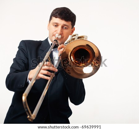 Young man playing his trombone. - stock photo