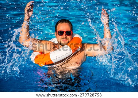 Young man playing in swimming pool. Summer vacation concept