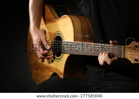Young man playing on acoustic guitar on dark background - stock photo
