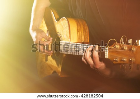 Young man playing on acoustic guitar on dark background with light effect - stock photo