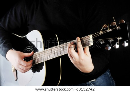 Young man playing on black  guitar. - stock photo