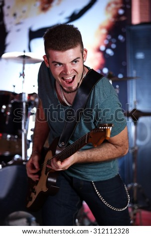 Young man playing on electric guitar at pub - stock photo