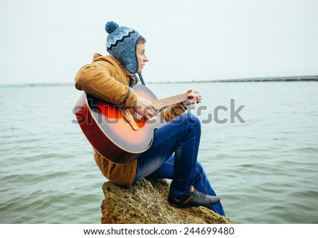 young man playing on guitar at the lake - stock photo