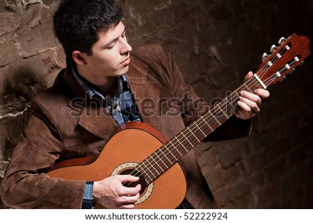 Young man playing on guitar. Camera angle view.