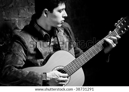 Young man playing on guitar. Dark black and white colors.