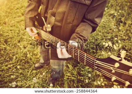 Young man playing on the guitar outdoors. Vintage, music concept - stock photo