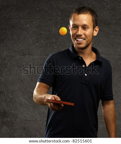 young man playing ping pong against a grunge background - stock photo
