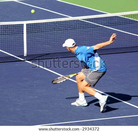 Young man playing professional tennis - stock photo