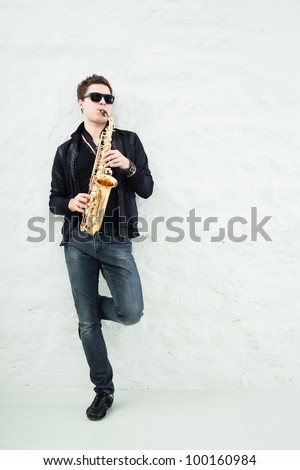 Young man playing sax laening against a wall - stock photo