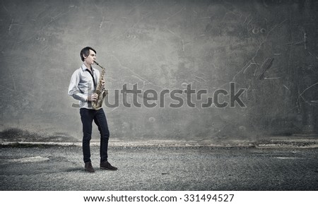 Young man playing saxophone in empty room
