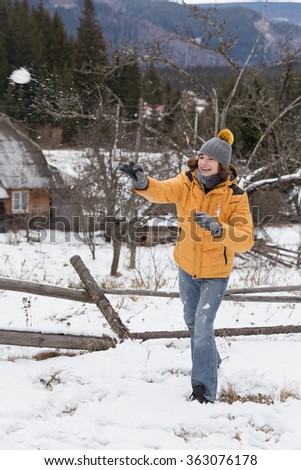 young man playing snowballs, a village in the Carpathian Mountains, Ukraine - stock photo