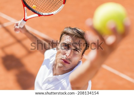Young man playing tennis - stock photo