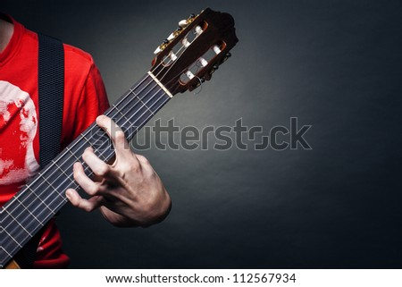 Young man playing the guitar.Guitarist hands in the foreground - stock photo