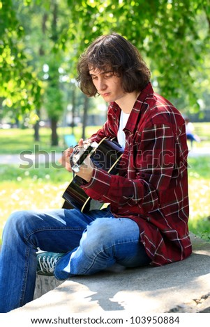 young man playing the guitar, outdoor