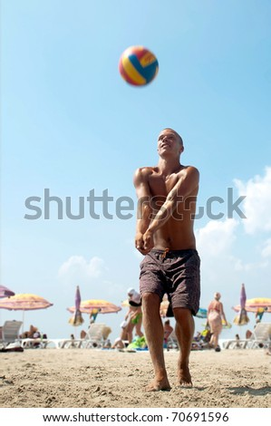 young man playing volleyball on a beach. - stock photo