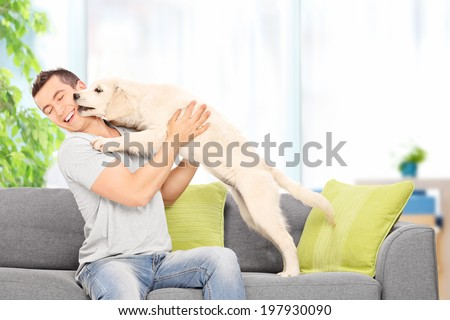 Young man playing with a puppy seated on couch at home - stock photo