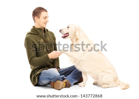 Young man playing with a retriever dog isolated on white background - stock photo