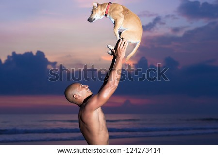 young man playing with dog on beach in Bali - stock photo