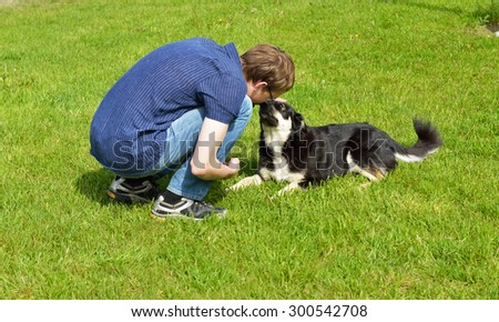 Young man playing with fun dog - stock photo