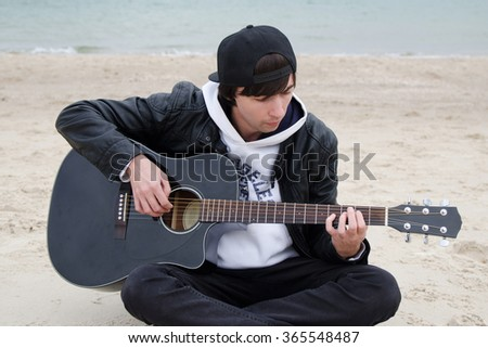 young man plays guitar at the beach