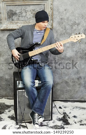 Young man plays guitar sitting on amplifier in room powdered with snow - stock photo