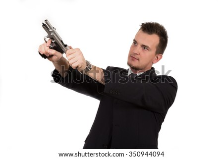 Young man pointing a gun isolated on white background - stock photo