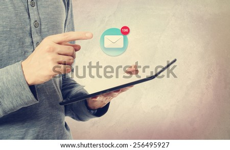 Young man pointing at an email icon over a tablet computer