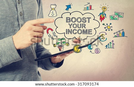 Young man pointing at Boost Your Income concept over a tablet computer - stock photo