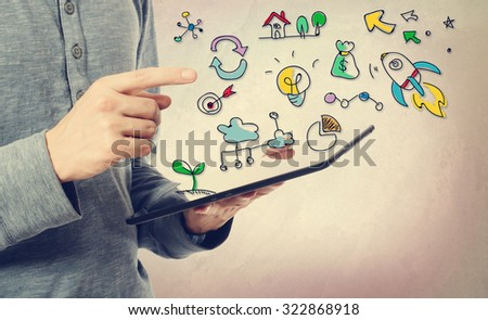 Young man pointing at Creativity concept over a tablet computer - stock photo