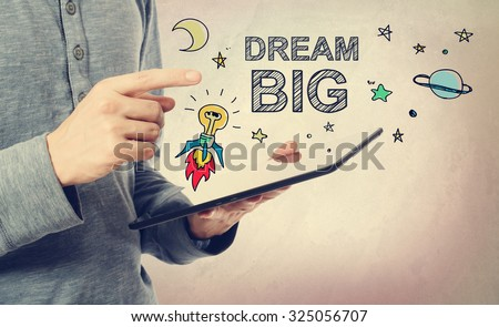 Young man pointing at Dream BIG concept over a tablet computer